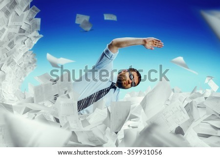Man swimming in papers