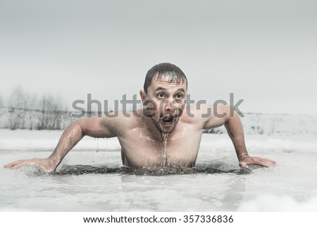 Man swimming in the ice hole with emotional face - stock photo