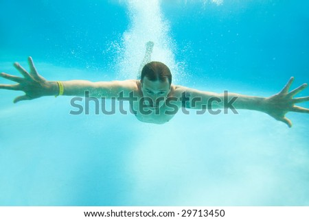 Man swimming under water in pool - stock photo