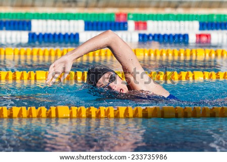 Man swims crawl in the pool, goggles, hat. - stock photo