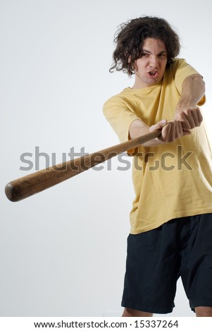 Man swinging a baseball bat wearing a silly expression on his face. Vertically framed photograph - stock photo