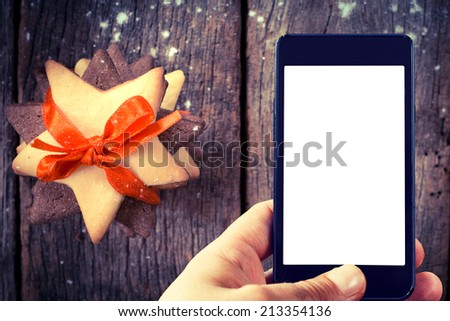 Man take the shoot with his cell phone of Christmas cookies.Selective focus on the cell phone - stock photo