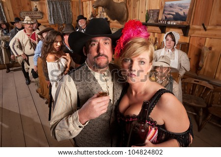 Man takes a drink with bar maid in old west tavern - stock photo
