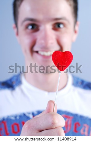 Man takes a red heart at blue background - stock photo