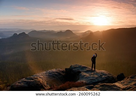 Man takes photos with smart phone on peak of rock empire. Dreamy fogy landscape, spring orange pink misty sunrise in a beautiful valley of Saxony Switzerland park. - stock photo