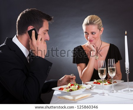 Man taking a mobile call during a romantic dinner in an elegant restaurant with the woman stretching her hand across the table as though to take it away from him - stock photo