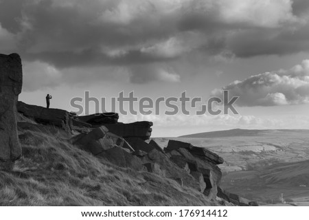 Man taking a photo at Buckstone edge calderdale west yorkshire - stock photo