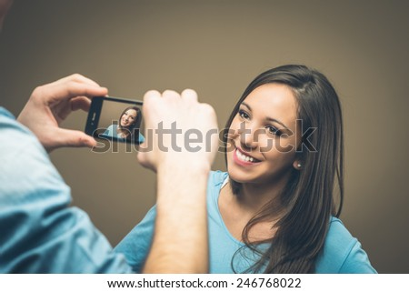 Man taking a picture of a beautiful young girl with his smartphone - stock photo