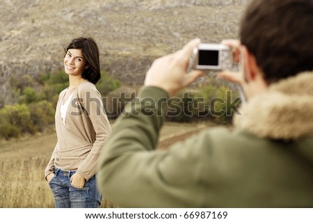 man taking a picture of his girlfriend - stock photo