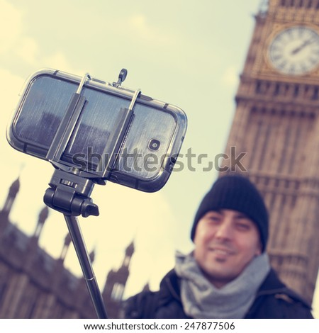 man taking a self-portrait with a selfie stick in front of the Big Ben in London, United Kingdom, with a filter effect