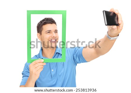 Man taking a selfie behind a picture frame with cell phone isolated on white background - stock photo