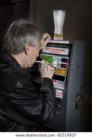 Man taking breathalyzer test at a bar - stock photo