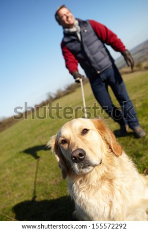 Man Taking Dog On Walk In Autumn Countryside - stock photo