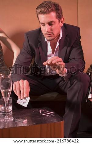Man taking drugs at a nightclub. - stock photo