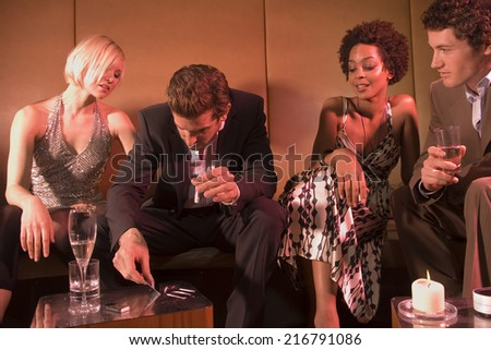 Man taking drugs at a nightclub. - stock photo