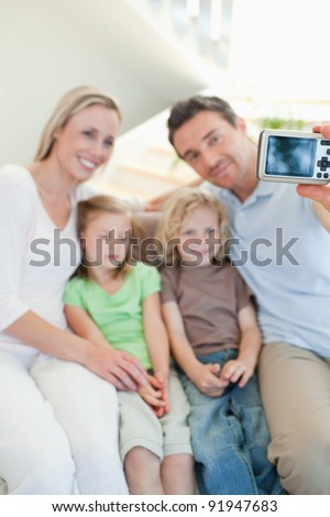 Man taking family picture on the sofa