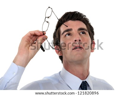 Man taking his glasses off and looking upwards - stock photo