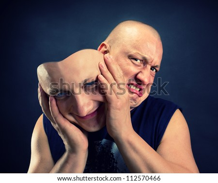 Man taking off his happy facial mask - stock photo