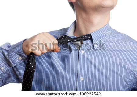 Man taking off neck tie - stock photo