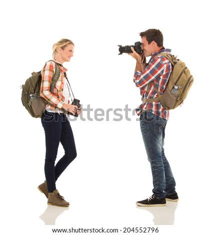 man taking photo of happy girlfriend on white background - stock photo