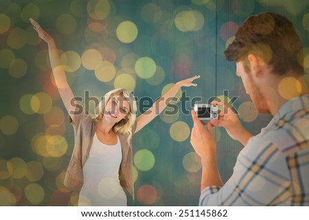 Man taking photo of his pretty girlfriend against close up of christmas lights - stock photo