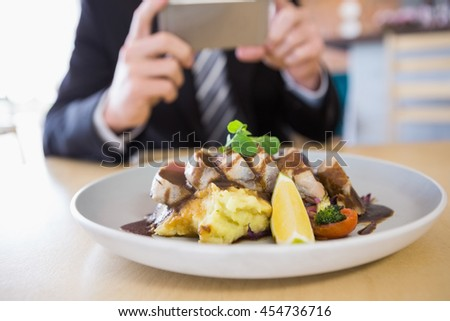 Man taking photograph of meal in restaurant