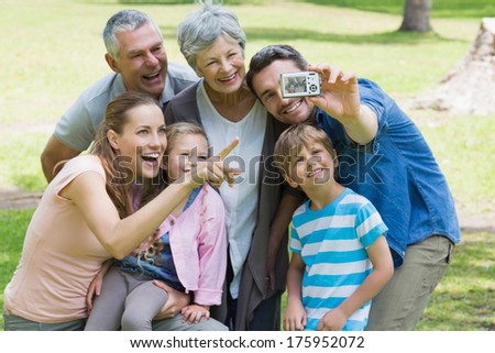 Man taking picture of his cheerful extended family at the park - stock photo