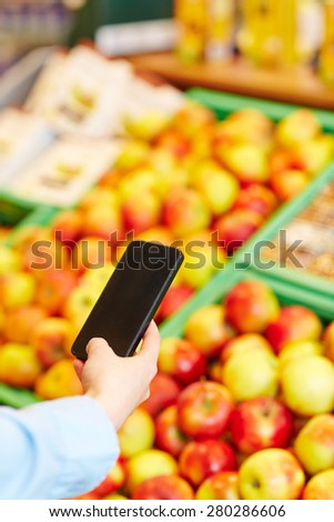 Man taking pictures of fresh apples with his smartphone in a supermarket