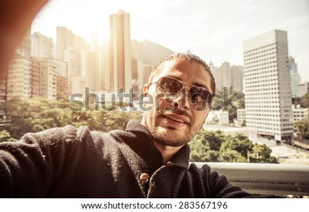 man taking selfie in hong kong. concept about travelers, technology and people - stock photo