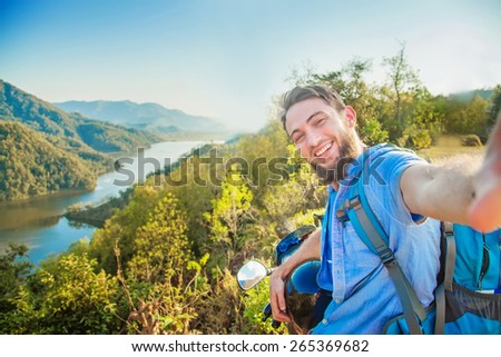 Man taking selfie sitting on his motorbike with mountains on a background, Nepal