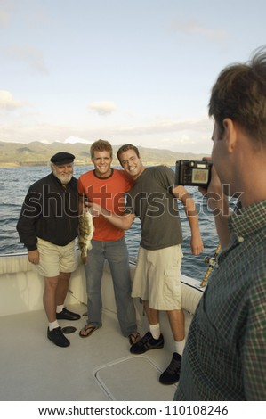 Man taking snapshot of friends with their catch on yacht - stock photo