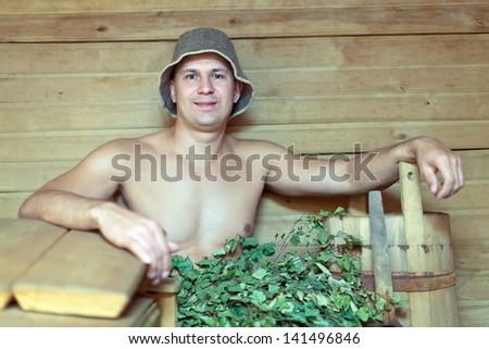 Man taking steam in wooden sauna - stock photo