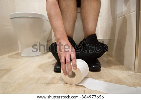 man taking with a roll of toilet paper in a toilet
