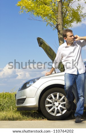 Man talking on a cell phone by a broken car - stock photo