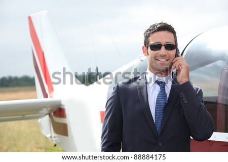 Man talking on a mobile phone next to a private plane - stock photo