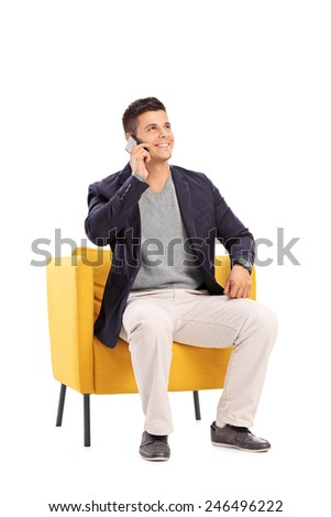 Man talking on a phone seated in a modern armchair isolated on white background