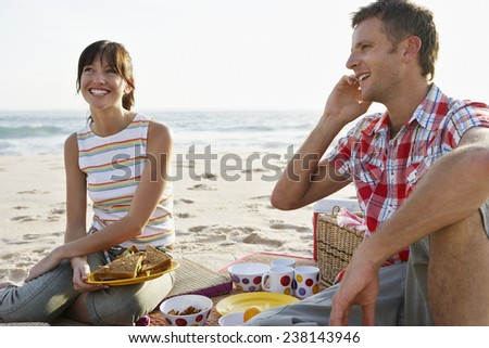 Man Talking on Cell Phone while Having Picnic on Beach - stock photo