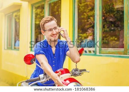 Man talking on phone on his motorbike - stock photo