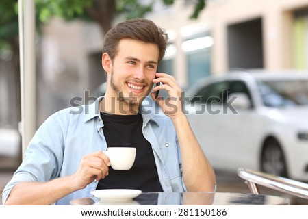 Man talking on the mobile phone in a coffee shop sitting in the terrace outdoors and holding a cup - stock photo