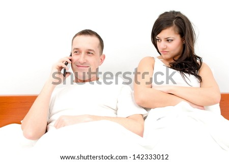 Man talking on the phone, woman upset - stock photo