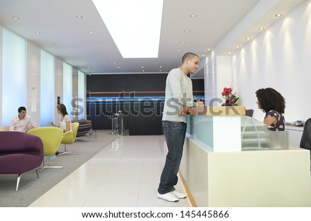 Man talking to receptionist at the reception desk in office - stock photo