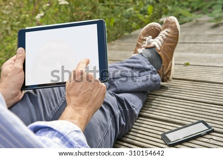 Man, tapping on a tablet, playing a game outdoors, sitting on a plank bridge, whith his phone next to him. Both can be used as presentation for mock-up apps, website and presentations. - stock photo