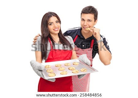 Man tasting the cookies baked by his girlfriend isolated on white background - stock photo