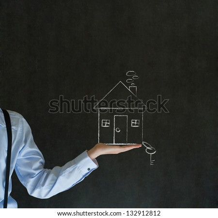 Man teacher, salesman, student or businessman holding chalk house, home or real estate with key - stock photo