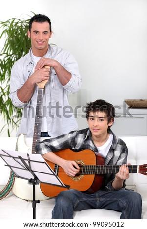Man teaching teenage boy the guitar - stock photo
