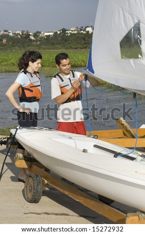 Man teaching woman how to sail with sailboat on trailer. Man showing woman sail rigging. Vertically framed photo - stock photo