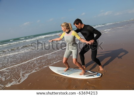 Man teaching young woman to surf - stock photo
