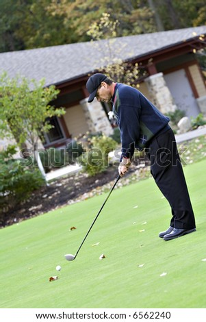Man teeing off in front of the golf club house on a beautiful fall day. - stock photo