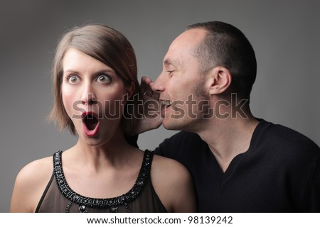 Man telling an astonished woman a secret