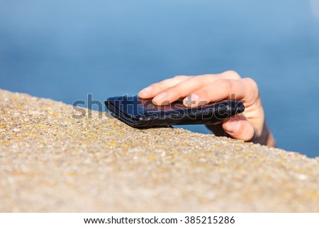 Man thief finding wallet on sea shore taking stealing it. Leaving belongings unattended and risk of theft - stock photo